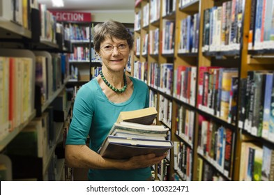 Active senior librarian woman holding books beside a bookshelf in  a library looking at camera. Real people. Copy space