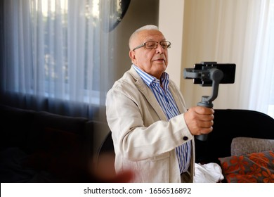 Active senior man 70-75 years old shooting video with smartphone and gimbal stabilizer at home. Elderly man taking selfie using cellphone. Concept of lifestyle, technology. Window on background.