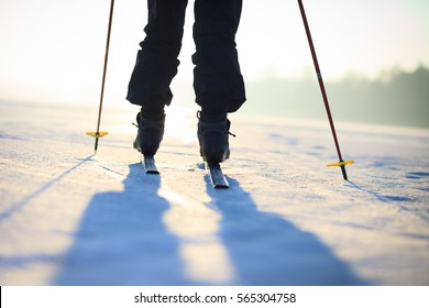 Active senior man cross-country skiing on huge snow meadow during lovely winter sunset