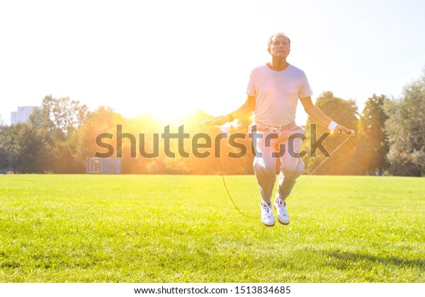 Active senior man doing jumping rope work out in park with yellow lens flare in background