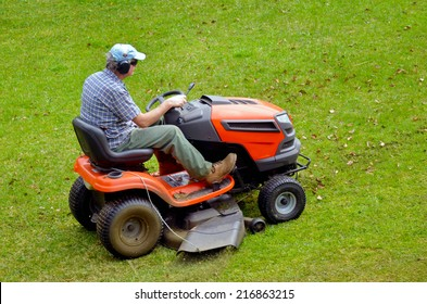 Active senior man gardener on ride-on lawn mower cutting grass. Real people. Copy spcace