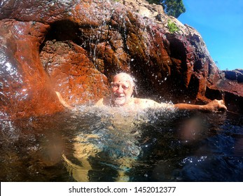 Active senior man having fun at  Wangi Falls in Litchfield National Park in the Northern Territory of Australia