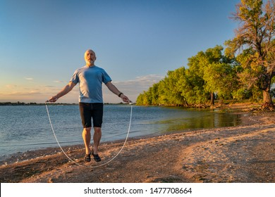 active senior man is jumping a heavy fitness jump rope on a lake beach, Boyd Lake State Park in northern Colorado