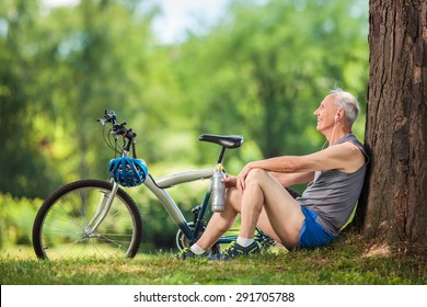 Active senior man listening to music on headphones seated by a tree in a park