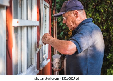 Active senior man painting window frame of wooden cabin. House improvemnet. Old craftsperson repairing house exterior.