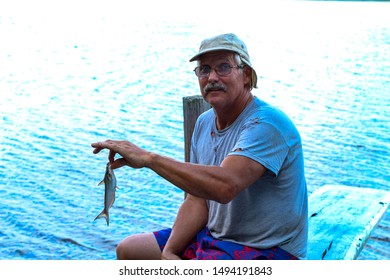 Active senior man proudly showing off the little catfish he caught on his summer vacation at the Mattaponi River in Virginia