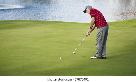Active senior man putting out on golf course beside lake.