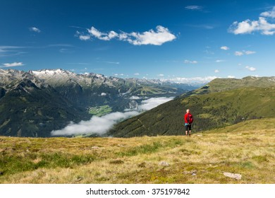 active senior man in retirement watching epic mountain scenery in austria alps near kaprun
