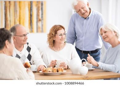 Active senior people eating dessert during a meeting in nursing home