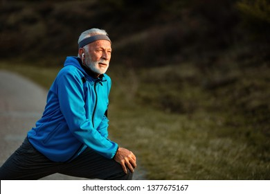 Active senior sportsman doing stretching exercise and warming up before sports training in nature. Copy space.