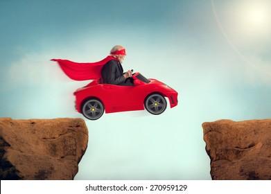 active senior superhero driving a car off a ravine