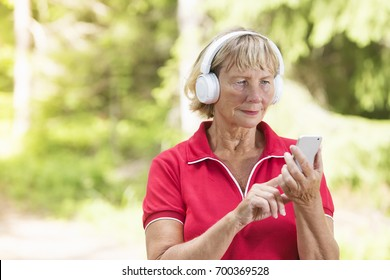 Active senior woman athlete checking sport tracking application from mobile phone wearing wireless headphones.
