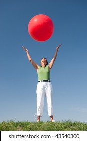 Active senior woman with a big red ball in front of blue sky