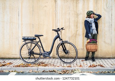 Active senior woman with electrobike standing outdoors in town, leaning against bike.