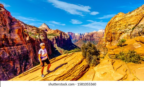 Active Senior Woman enjoying the view of the mountains surrounding Zion Canyon from the top of the Canyon Overlook Trail in Zion National Park, Utah, United States