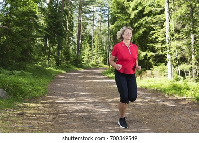 Active senior woman exercising. Jogging through the forest on running track listening music at bright sunny afternoon.