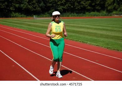 Active senior woman jogging in stadium