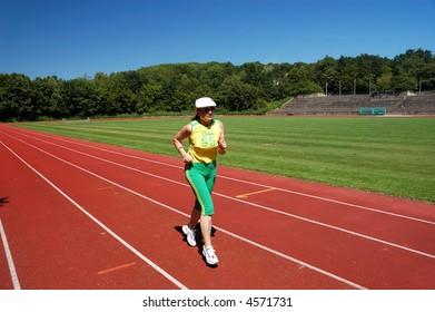 Active senior woman jogging in the stadium
