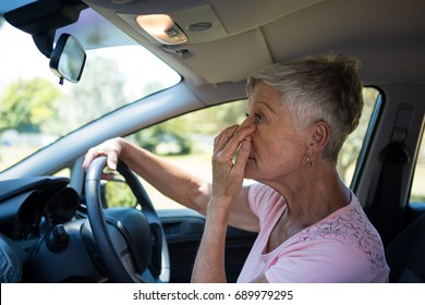 Active senior woman looking into rear view mirror while driving a car