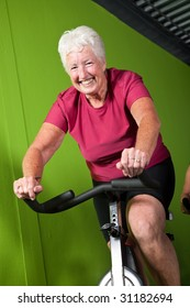 Active senior woman on bike in the gym