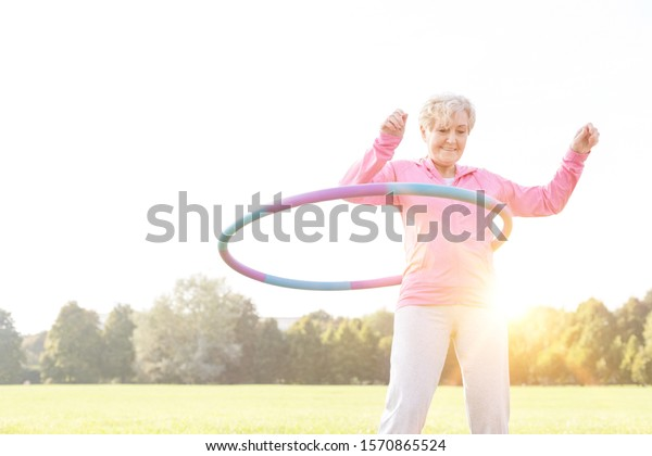 Active senior woman playing hula hooping in park with yellow lens flare