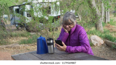 Active senior woman resting on park bench texting on smart phone in nature