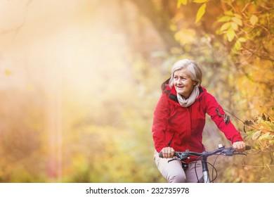 Active senior woman ridding bike in autumn nature.