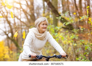 Active senior woman riding bike in autumn nature.
