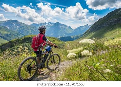 active senior woman, riding her e-mountainbike in the Arlberg area near the famous village of Lech, Tirol, Austrian Alps