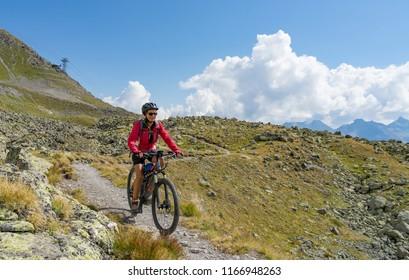 active senior woman, riding her e-mountainbike on the famous Suvretta Loop trail, high above Saint Moritz, Engadin, Switzerland
