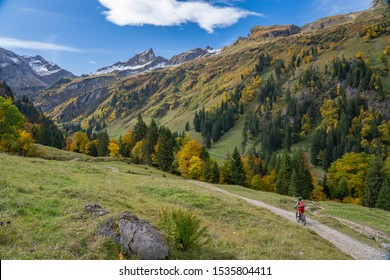 active senior woman riding her electric mountain bike in the autumnal atmosphere of the Allgau mountains near Hindeland, Bavaria, Germany