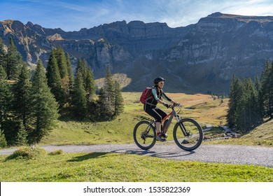 active senior woman riding her electric mountain bike in the autumnal atmosphere ofBregenz Forest mountains near Mellau, Vorarlberg, Austria