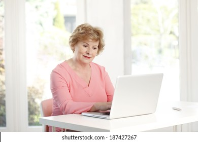 Active senior woman sitting at desk and using laptop.