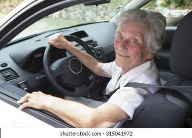 Active senior woman smiling while driving car