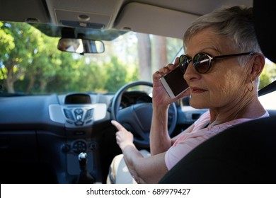 Active senior woman talking on mobile phone in car