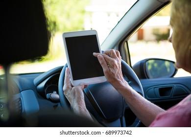 Active senior woman using digital tablet in car