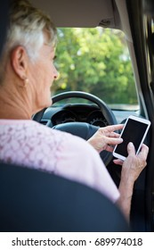 Active senior woman using mobile phone while driving a car