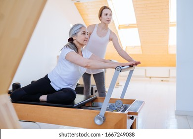 Active senior woman working exercise in the gym. Personal trainer helping senior woman. Workout in pilates studio..