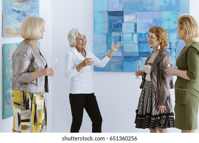 Active senior women on painting opening in museum