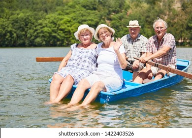 Active seniors group takes a boat trip in rowing boat in the summer on the lake
