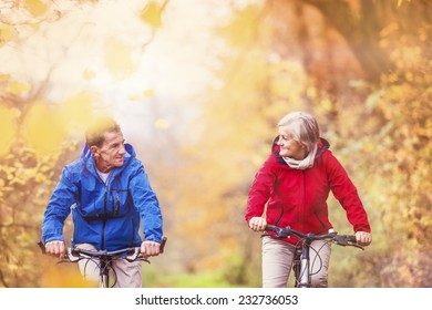 Active seniors ridding bike in autumn nature. They relax outdoor.