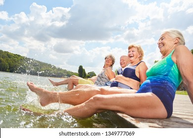 Active seniors splashing with their feet in the water during a summer vacation at the bathing lake