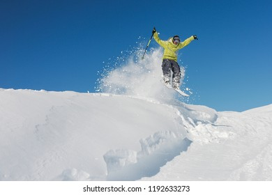 Active skier dressed in bright yellow sportswear riding down the mountain slope in Georgia, Gudauri on sunny day