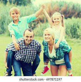 Active smiling family with two children spending summer day at the lawn