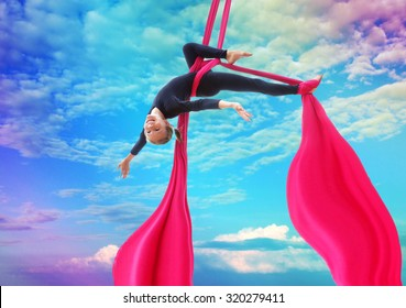 Active smiling sportive cheerful child training dancing performing on aerial silks or ribbons, hanging upside down in the blue rainbow sky Childhood, sports, happiness, active lifestyle concept.