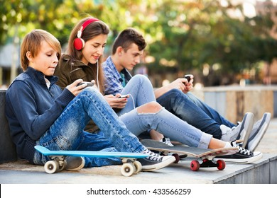 Active smiling teens playing on smarthphones and listening to music