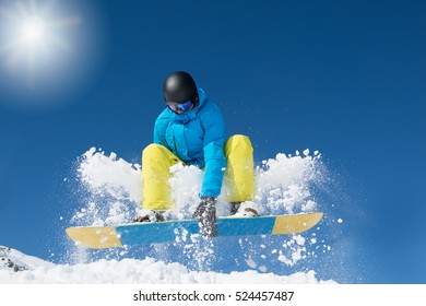 Active snowboarder jumping in winter mountains