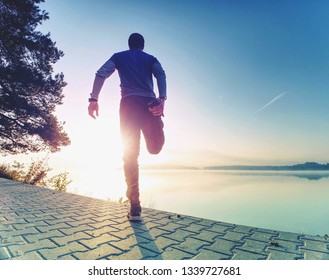 Active sport man runner stretching body on pavement lake side, regular outdoor training for marathon