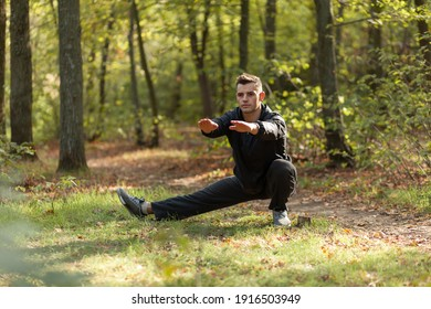 Active sport man trains warm-up exercises in the autumn forest. Healthy lifestyle. Outdoor workout
