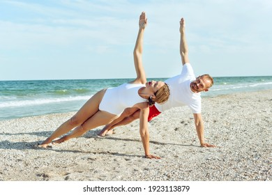 Active sports lifestyle. Smiling couple doing yoga exercises outdoors at the beach pier. Morning workout people doing yoga exercise